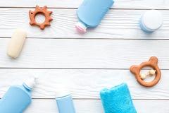 Cosméticos hipoalérgicos naturales del ` s de los niños Botellas, toalla y juguetes en el copyspace de madera blanco de la opinió Imágenes de archivo libres de regalías