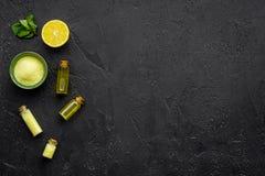 Cosméticos naturais do citrino Óleo dos termas perto do limão no modelo preto da opinião superior do fundo Foto de Stock