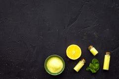 Cosméticos naturais do citrino Óleo dos termas perto do limão no modelo preto da opinião superior do fundo Imagem de Stock Royalty Free