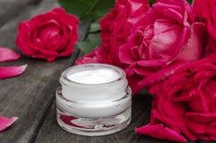 Cosméticos naturales de la flor con las flores rosadas rojas para el cuidado de la cara y del cuerpo en un tarro de cristal en un foto de archivo