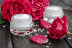 Cosméticos naturales de la flor con las flores rosadas rojas para el cuidado de la cara y del cuerpo en un tarro de cristal en un fotografía de archivo