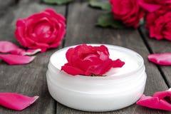 Cosméticos naturales de la flor con las flores rosadas rojas para el cuidado de la cara y del cuerpo en un tarro de cristal en un foto de archivo libre de regalías