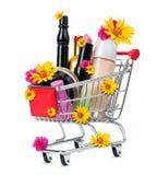 Cosméticos no carrinho de compras com flores Fotografia de Stock Royalty Free