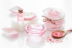 Cosméticos orgánicos de Rose con la sal, la crema y el aceite en el fondo blanco de la tabla imagenes de archivo