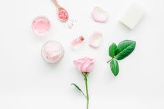 Cosméticos orgánicos de Rose con la sal, la crema y el aceite en la mofa blanca de la opinión superior del fondo de la tabla para Imagen de archivo