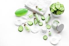 Cosméticos orgánicos frescos con el pepino Crema y loción en el copyspace blanco del fondo Fotografía de archivo