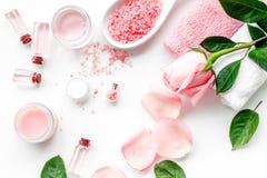 Cosméticos orgánicos naturales con aceite color de rosa Crema, loción, sal del balneario en la opinión superior del fondo blanco Foto de archivo