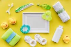 Cosméticos para el baño, el marco, la toalla y los juguetes del bebé en el espacio amarillo de la opinión superior del fondo para Fotos de archivo