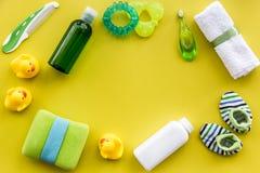 Cosméticos para el baño, la toalla y los juguetes del bebé en el espacio amarillo de la opinión superior del fondo para el texto Imagen de archivo libre de regalías