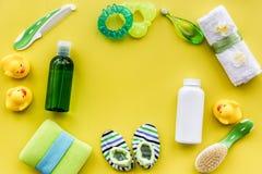 Cosméticos para el baño, la toalla y los juguetes del bebé en el espacio amarillo de la opinión superior del fondo para el texto Fotografía de archivo libre de regalías