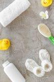 Cosméticos para el baño, la toalla y los juguetes del bebé en el espacio gris de la opinión superior del fondo para el texto Imagen de archivo