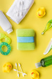 cosméticos para el baño, la toalla y los juguetes del bebé en modelo amarillo de la opinión superior del fondo Imagen de archivo libre de regalías