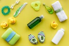 cosméticos para el baño, la toalla y los juguetes del bebé en modelo amarillo de la opinión superior del fondo Foto de archivo