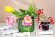 Cosméticos para el cuerpo y pelo y flores Foto de archivo libre de regalías