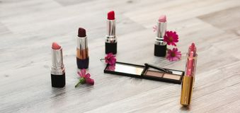 Cosméticos para el maquillaje y accesorios en un fondo blanco con una copia, una visión superior y flores en el fondo Foto de archivo