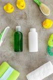 Cosméticos para o banho, a toalha e os brinquedos do bebê na opinião superior do fundo cinzento Fotografia de Stock Royalty Free