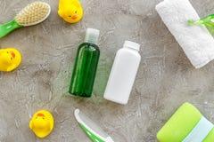 Cosméticos para o banho, a toalha e os brinquedos do bebê na opinião superior do fundo cinzento Imagem de Stock Royalty Free
