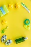 Cosméticos para o banho, a toalha e os brinquedos do bebê no espaço amarelo da opinião superior do fundo para o texto Fotografia de Stock Royalty Free