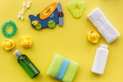 Cosméticos para o banho, a toalha e os brinquedos do bebê no espaço amarelo da opinião superior do fundo para o texto Fotos de Stock Royalty Free