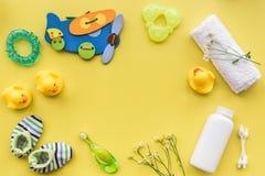 Cosméticos para o banho, a toalha e os brinquedos do bebê no espaço amarelo da opinião superior do fundo para o texto Foto de Stock