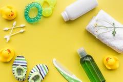 Cosméticos para o banho, a toalha e os brinquedos do bebê no espaço amarelo da opinião superior do fundo para o texto Imagem de Stock