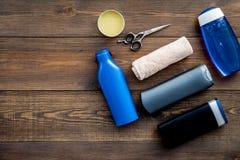 Cosméticos para o cabelo do ` s dos homens Garrafas com champô e gel, ferramentas para escovar no espaço de madeira escuro da cóp imagens de stock royalty free