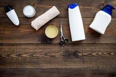 Cosméticos para o cabelo do ` s dos homens Garrafas com champô e gel, ferramentas para escovar no espaço de madeira escuro da cóp foto de stock royalty free