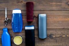 Cosméticos para o cabelo do ` s dos homens Garrafas com champô e gel, ferramentas para escovar no espaço de madeira escuro da cóp imagem de stock royalty free