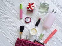 Cosméticos planos cosméticos del envase de la laca del producto de maquillaje del bolso en de madera blanco Fotos de archivo libres de regalías