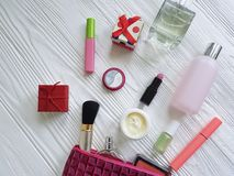 cosméticos planos del envase del decorativ del maquillaje cosmético del bolso en de madera blanco Imagen de archivo libre de regalías