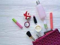 cosméticos planos del envase del lápiz labial del decorativ del maquillaje cosmético del bolso en de madera blanco Fotografía de archivo libre de regalías