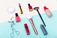 Cosméticos, productos de maquillaje y cepillos decorativos en fondo azul en colores pastel del color fotos de archivo