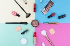 Cosméticos, productos de maquillaje y cepillos decorativos en fondo del color en colores pastel imagen de archivo libre de regalías