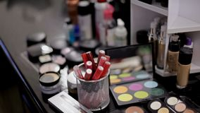 Cosméticos profesionales en el salón del maquillaje Cosméticos lujosos para el maquillaje Lápiz labial multicolor, sombras, polvo metrajes