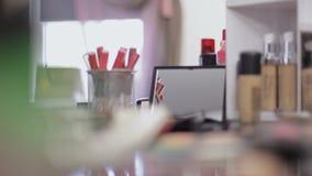 Cosméticos profesionales en el salón del maquillaje Cosméticos lujosos para el maquillaje Lápiz labial multicolor, sombras, polvo almacen de metraje de vídeo