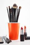 Cepillos y cosméticos del maquillaje en un fondo blanco Imagen de archivo