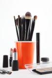 Cepillos y cosméticos del maquillaje en un fondo blanco Fotografía de archivo libre de regalías