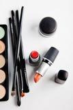 Cepillos y cosméticos del maquillaje en un fondo blanco Fotos de archivo libres de regalías