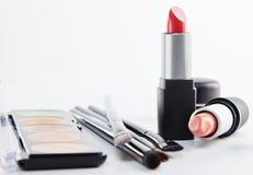 Cepillos y cosméticos del maquillaje en un fondo blanco Imágenes de archivo libres de regalías