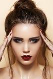 Cosméticos y maquillaje. Modelo atractivo con el pelo de la manera foto de archivo