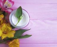 Cosmétique crème, alstroemeria de fleur sur un woodencleaner photographie stock