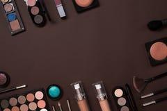 Cosmétiques colorés sur le lieu de travail brun avec l'espace de copie Les cosmétiques composent des objets d'artiste : rouge à l Photos stock