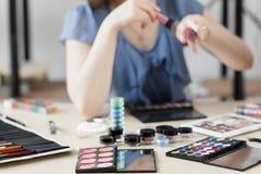 Cosmétiques colorés sur le lieu de travail de styliste photographie stock