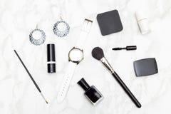 Cosmétiques et accessoires noirs et blancs sur un fond de marbre Photographie stock libre de droits