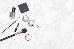 Cosmétiques et accessoires noirs et blancs sur un fond de marbre Image stock