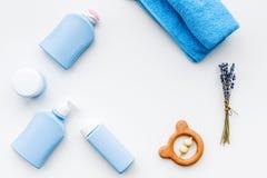 Cosmétiques naturels de bain pour des enfants Bouteilles, serviette et jouets sur le copyspace blanc de vue supérieure de fond Photo stock