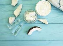 Cosmétiques organiques de peau de noix de coco de bio bouteille essentielle aromatique crème d'huile sur en bois bleu Photographie stock libre de droits