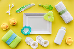Cosmétiques pour le bain, le cadre, la serviette et les jouets de bébé sur l'espace jaune de vue supérieure de fond pour le texte Photos stock