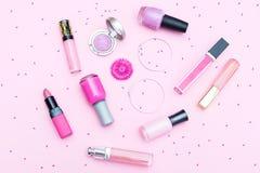 Cosmétiques roses de maquillage sur un fond rose Configuration plate photos stock