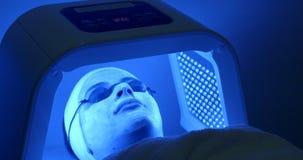 Cosmétologie et traitement facial Thérapie légère menée pour la femme avec le masque et les verres dans le salon professionnel Vu banque de vidéos